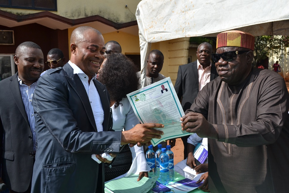 Chief Dan Okenyi, Commissioner for Lands and Survey (right) presenting Certificate of Occupancy to Frank Onyisi Nwongo one of the beneficiary  during the presentation of Certificate of Occupancy (C of O) to the Beneficiaries in Asaba